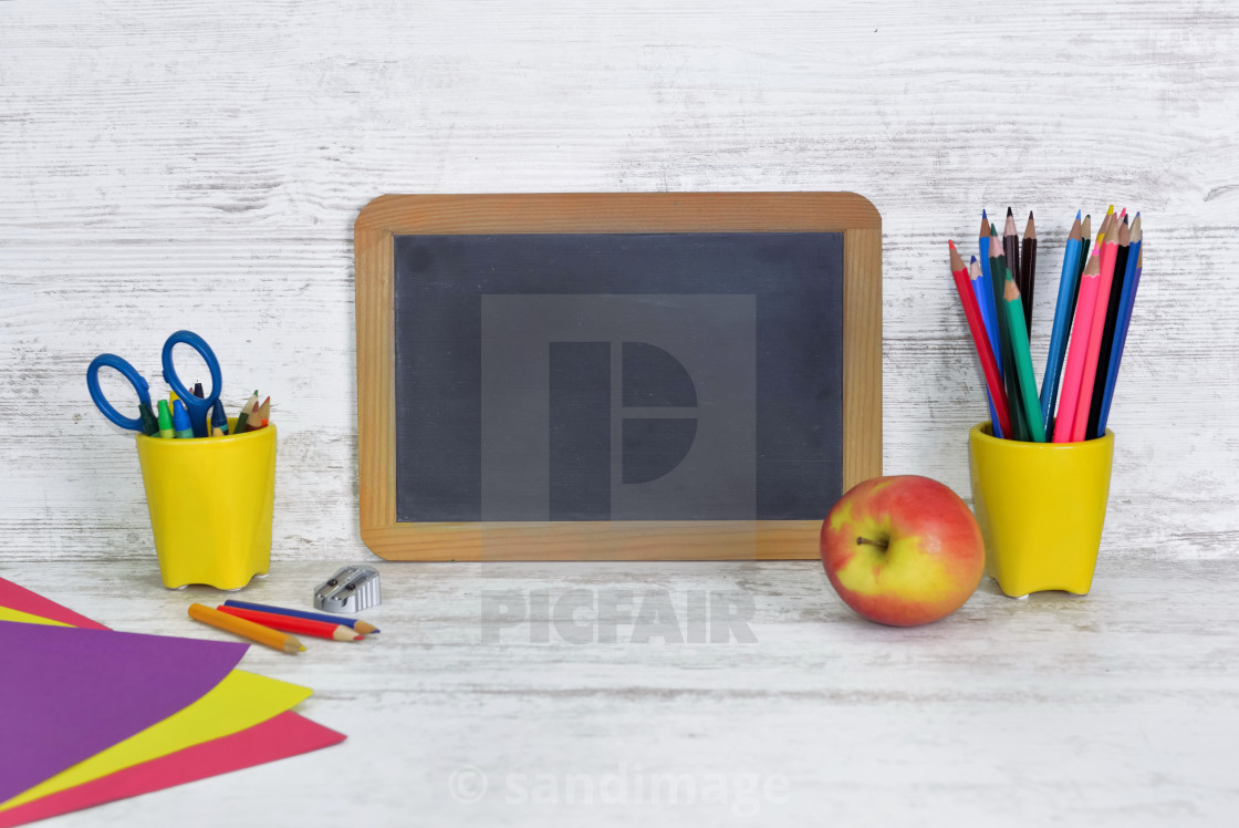 """""""black board on a kid desk with colorful pencils in yellow pot and an apple"""" stock image"""