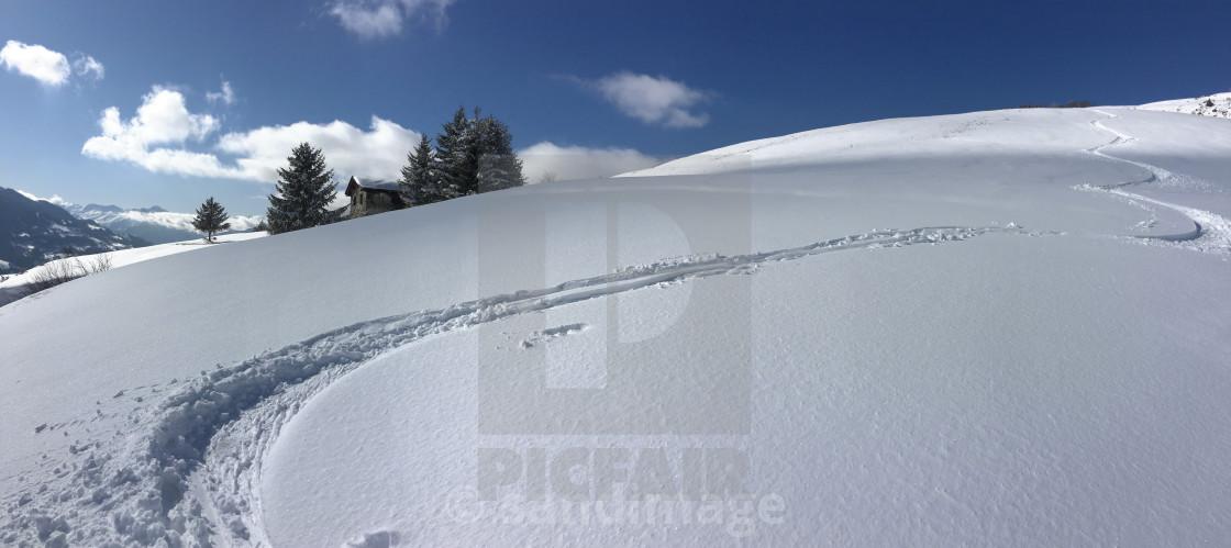 """ski prints on fresh snow covered mountain under blue sky"" stock image"