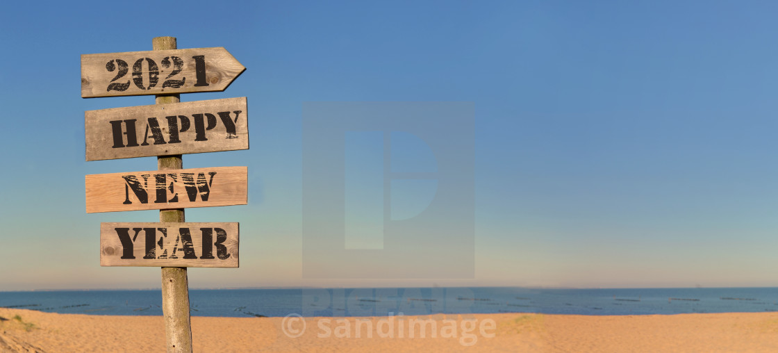 """""""2021 happy new year writing on a wooden post sign on the beach in panoramic view"""" stock image"""