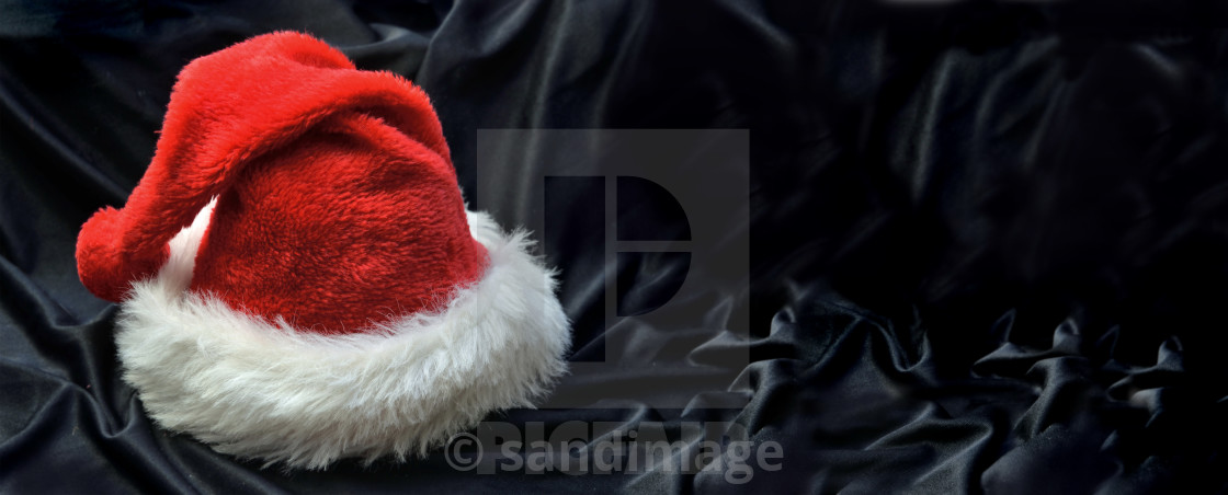 """red santa claus hat in black textile background"" stock image"
