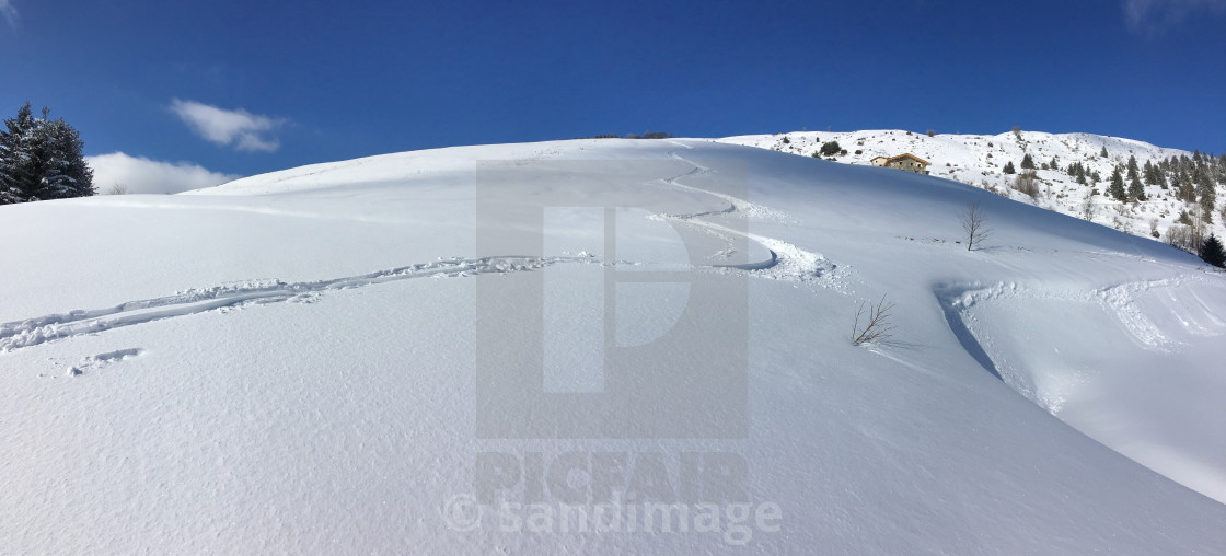 """ski prints on fresh snow covered mountain under blue sky"" stock image"