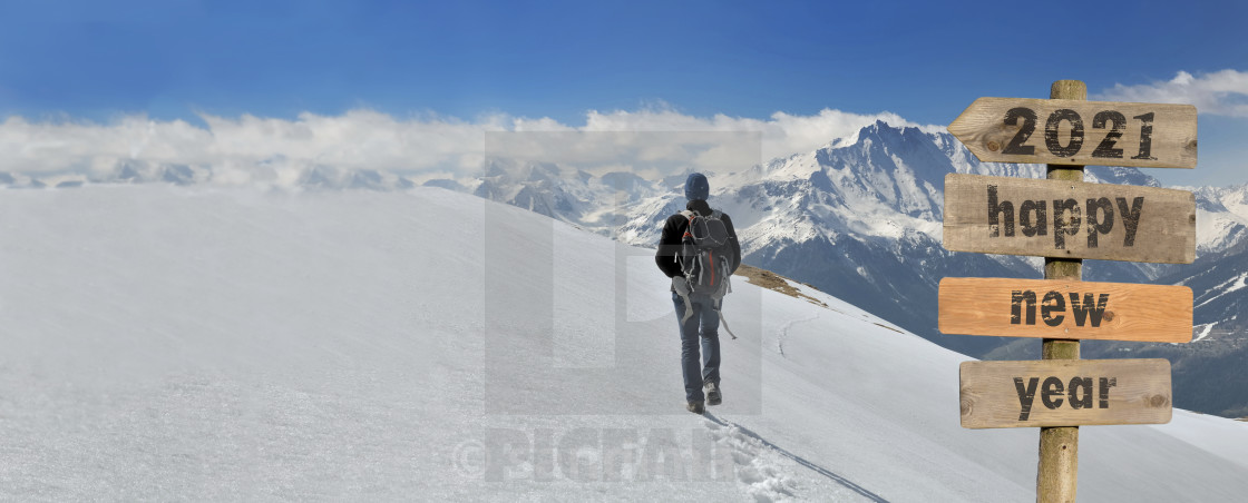 """""""2021 happy new year wrtten on a postsign with a hiker walking on the snow"""" stock image"""