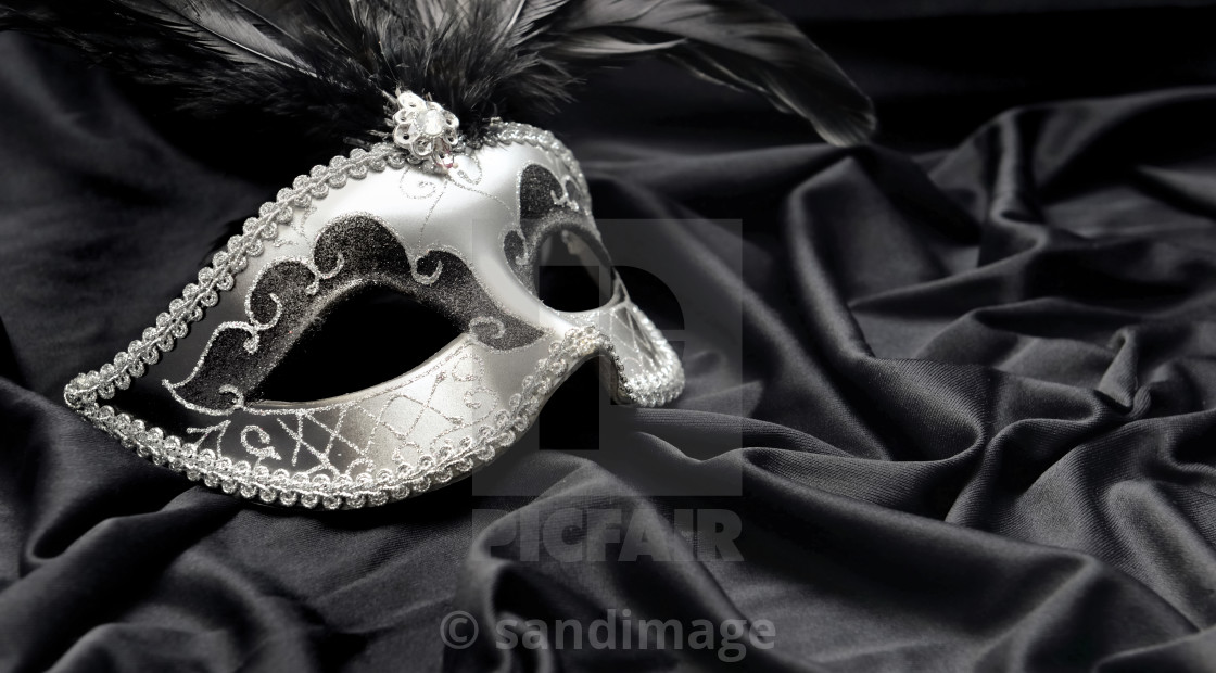 """carnival mak with feather on dark satin fabric background"" stock image"