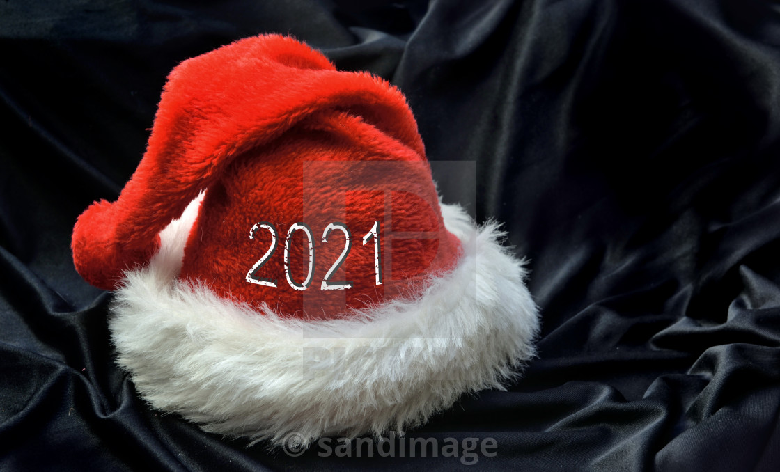 """""""2021 on red santa claus hat in black textile background"""" stock image"""