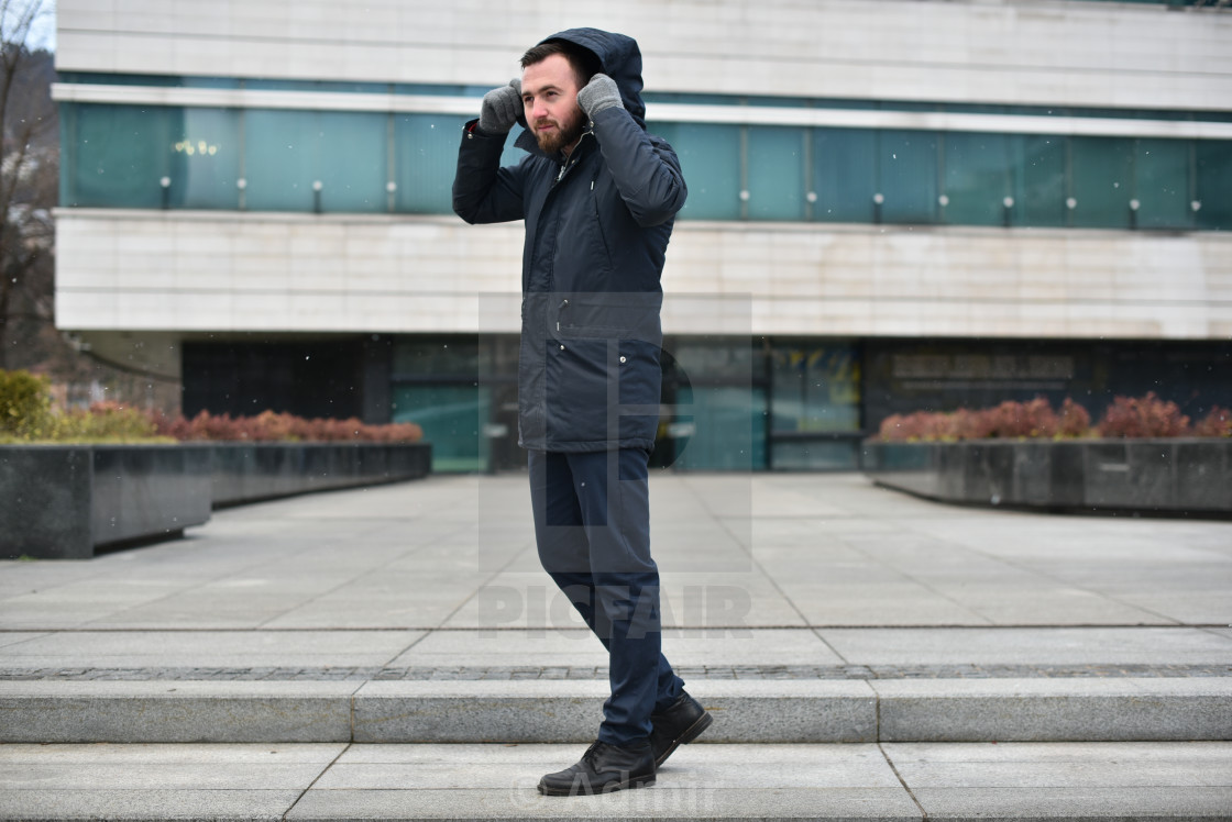 """young man on steps in winter clothes"" stock image"