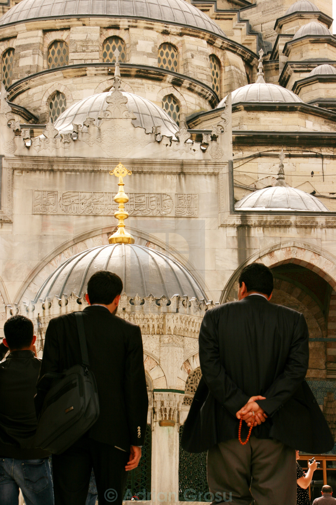 """Three muslims entering Yeni Cami (The New Mosque) in Istanbul, Turkey"" stock image"