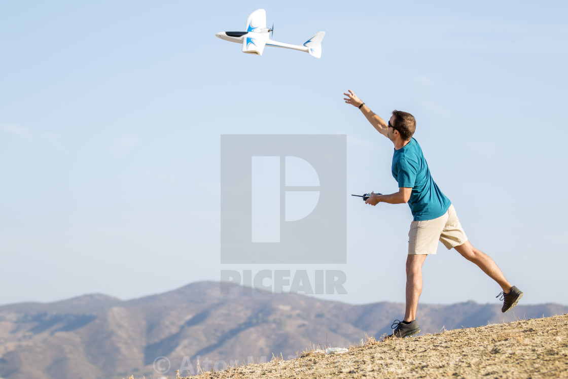 """Young man setting remote control plane in air"" stock image"
