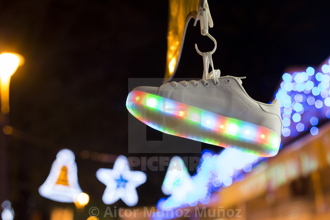 """Sportive shoe hanging on blurred background of lights in dark"" stock image"