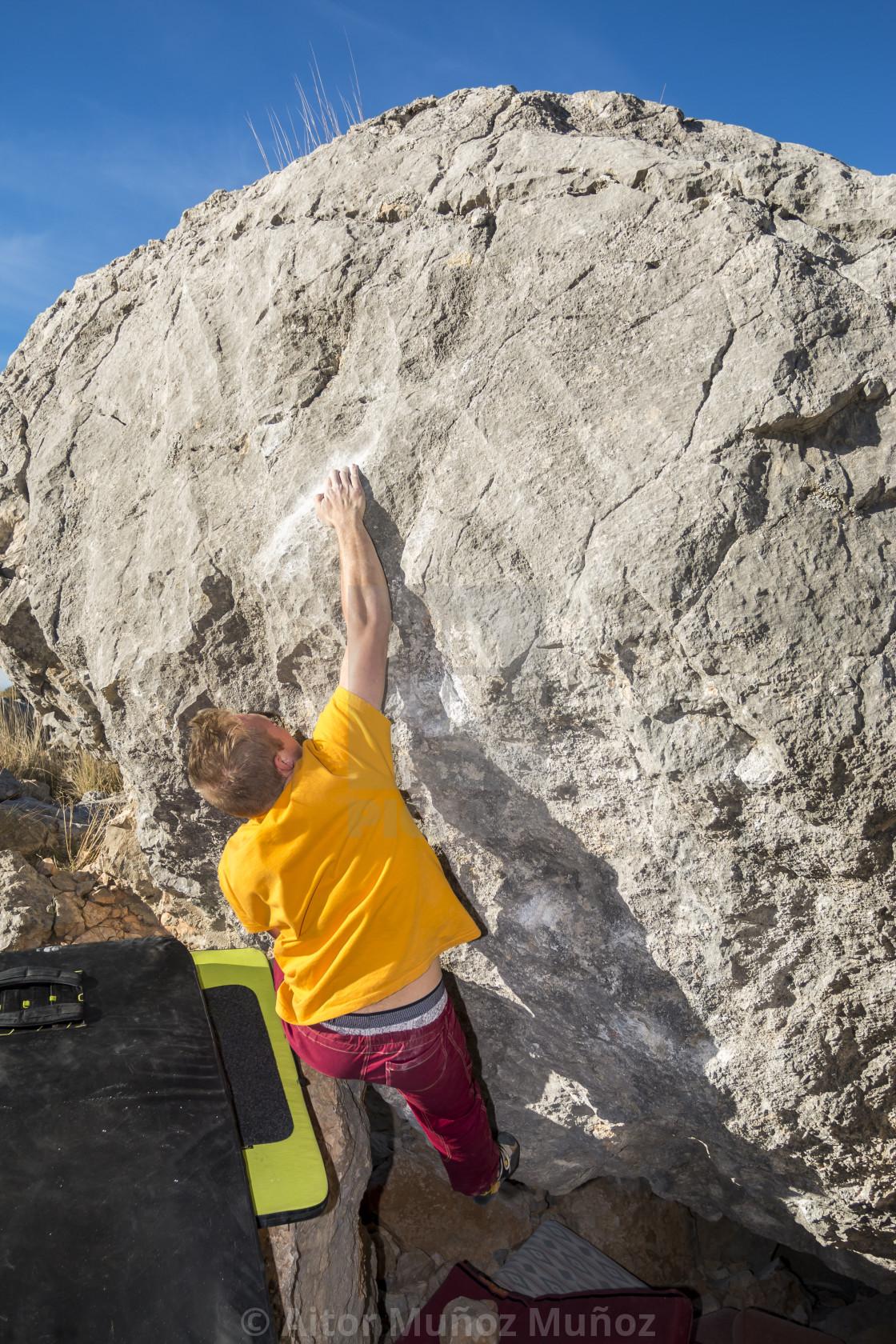 """Back view of man climbing rock bouldering"" stock image"