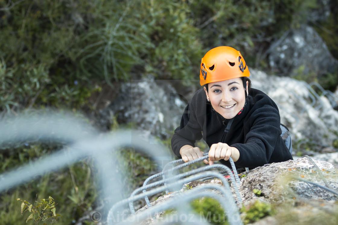 """Woman climbing up a via ferrata"" stock image"