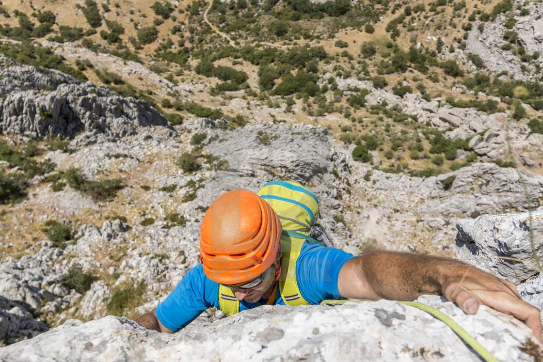 """Backpacker climbing on mountain"" stock image"