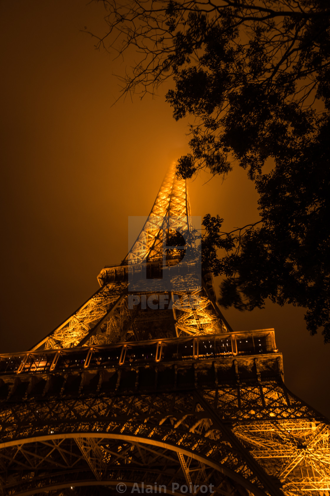 """Eiffel Tower at night / summit in the clouds"" stock image"