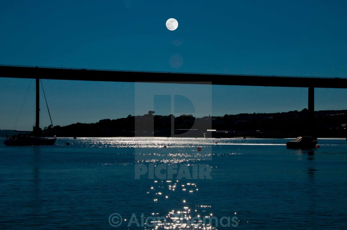 """Full silver moon over the Cleddau bridge at Milford Haven, Pembroke"" stock image"