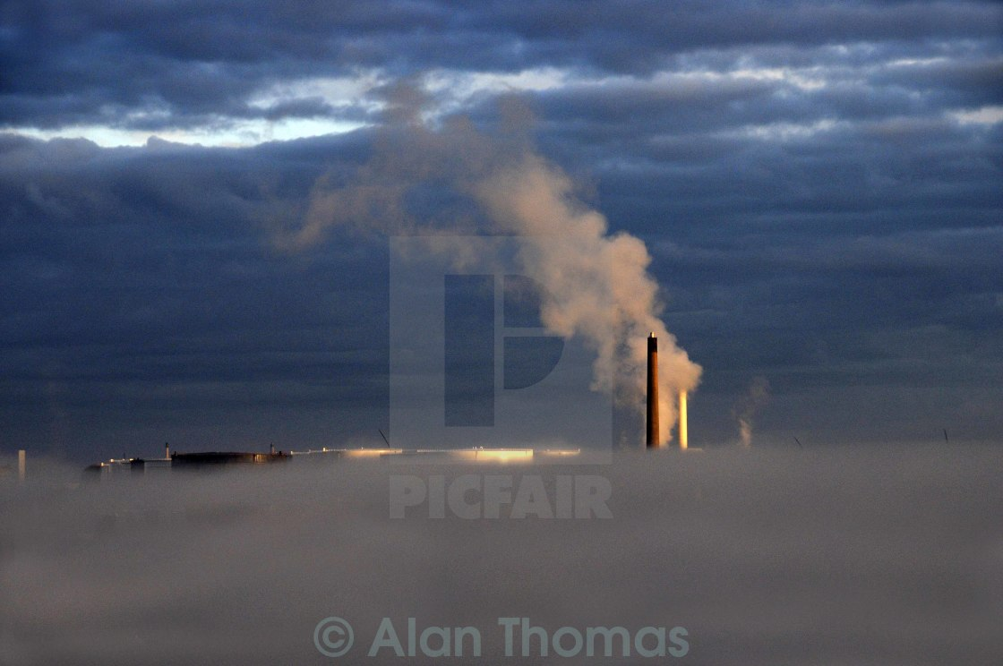 """Morning mist beneath a smoking chimney stack in an oil refinery"" stock image"