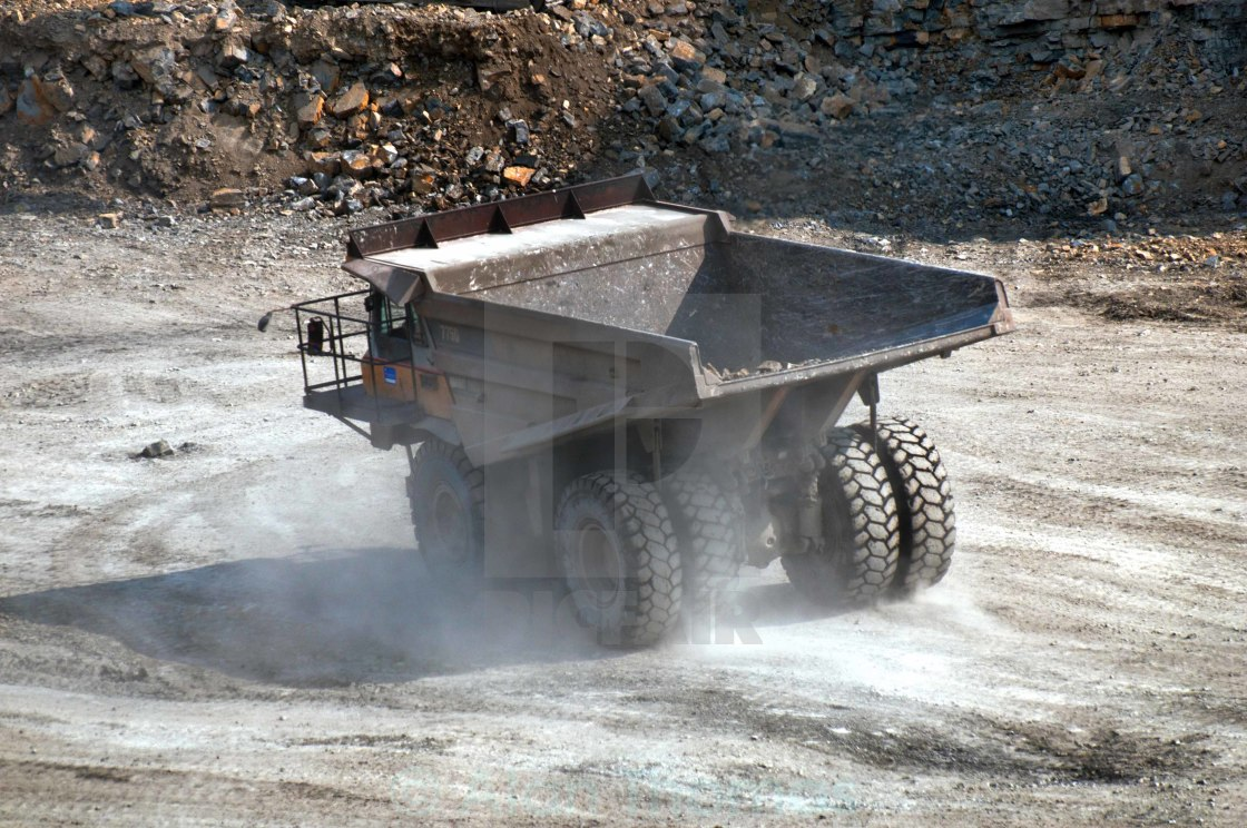 """""""Dump truck travelling on a road at a quarry site creating dust"""" stock image"""