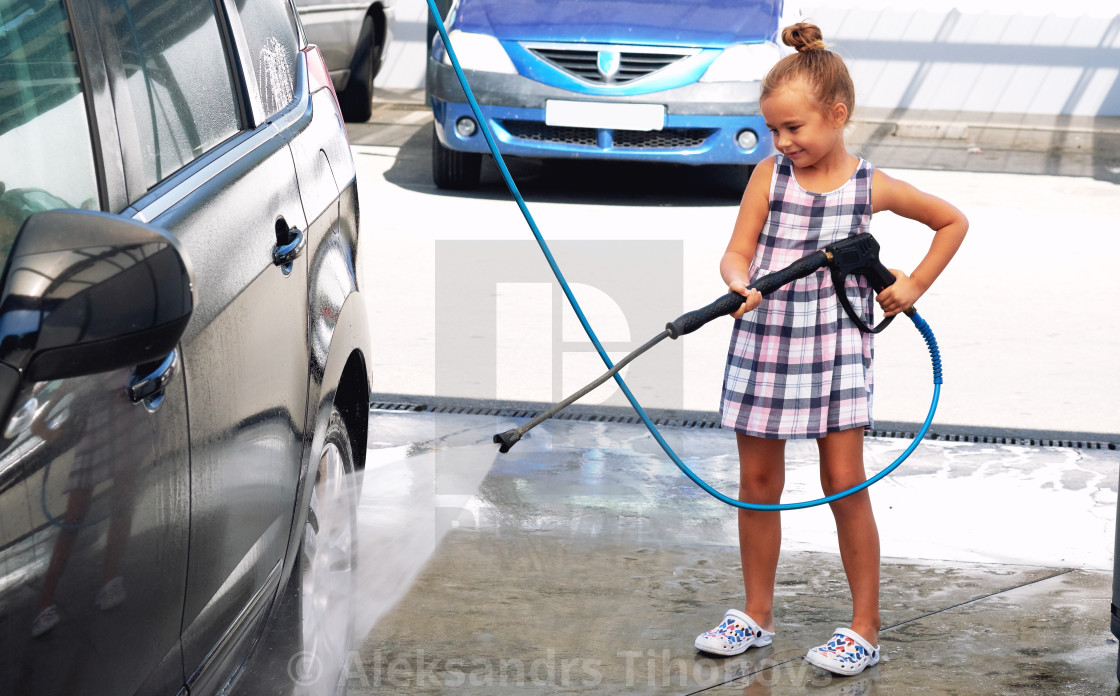 Little girl washing auto in self-serve car wash - License