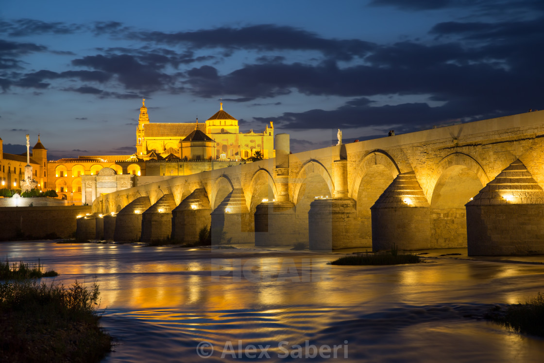 """""""The roman bridge of Cordoba with Cordoba's great cathedral and mosque at dusk."""" stock image"""