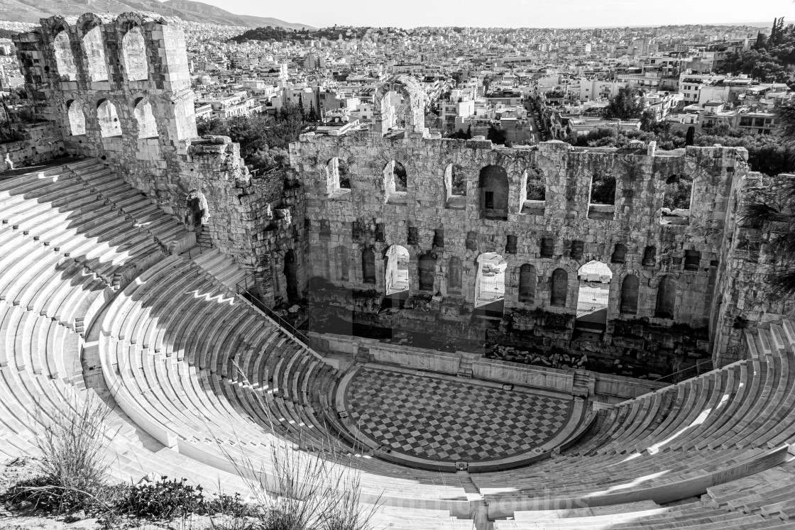 """""""Greyscale of the Odeon of Herodes Atticus with a city on the background in Greece"""" stock image"""