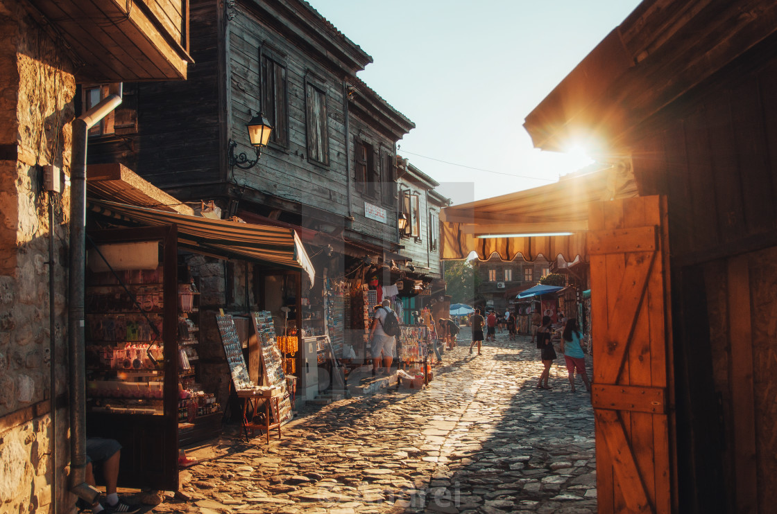 """People walk through streets of ancient nesebar at sunset."" stock image"