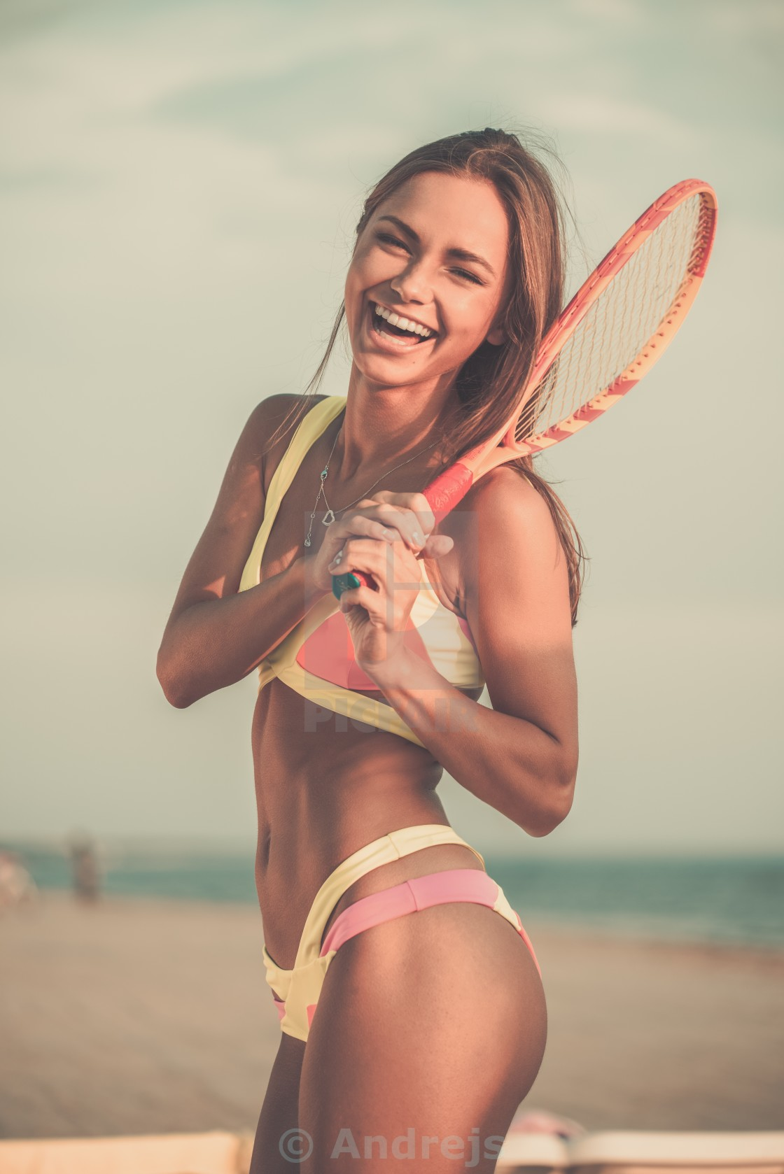 """Young girl in swimming suit on a beach with racquet"" stock image"