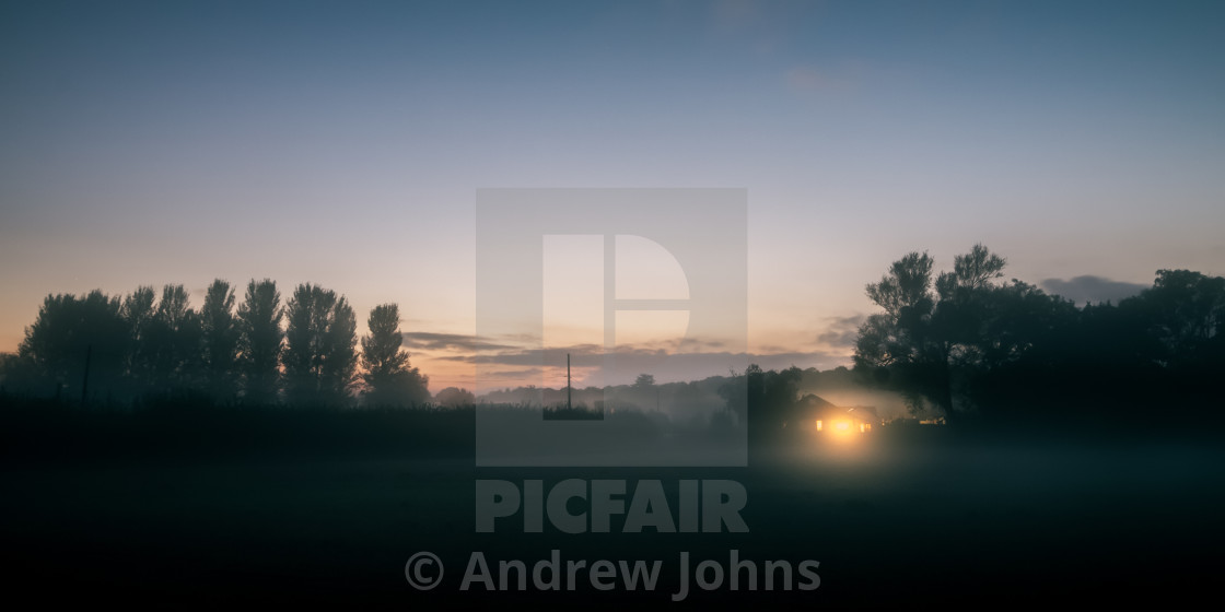 """Warm glow over a misty field"" stock image"