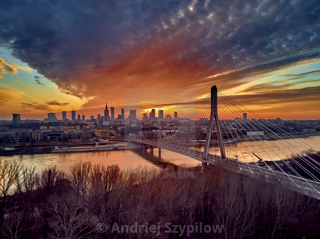 """Beautiful panoramic aerial drone sunset view to Warsaw city center with skyscrapers and Swietokrzyski Bridge (En: Holy Cross Bridge) - is a cable-stayed bridge over the Vistula river in Warsaw, Poland"" stock image"