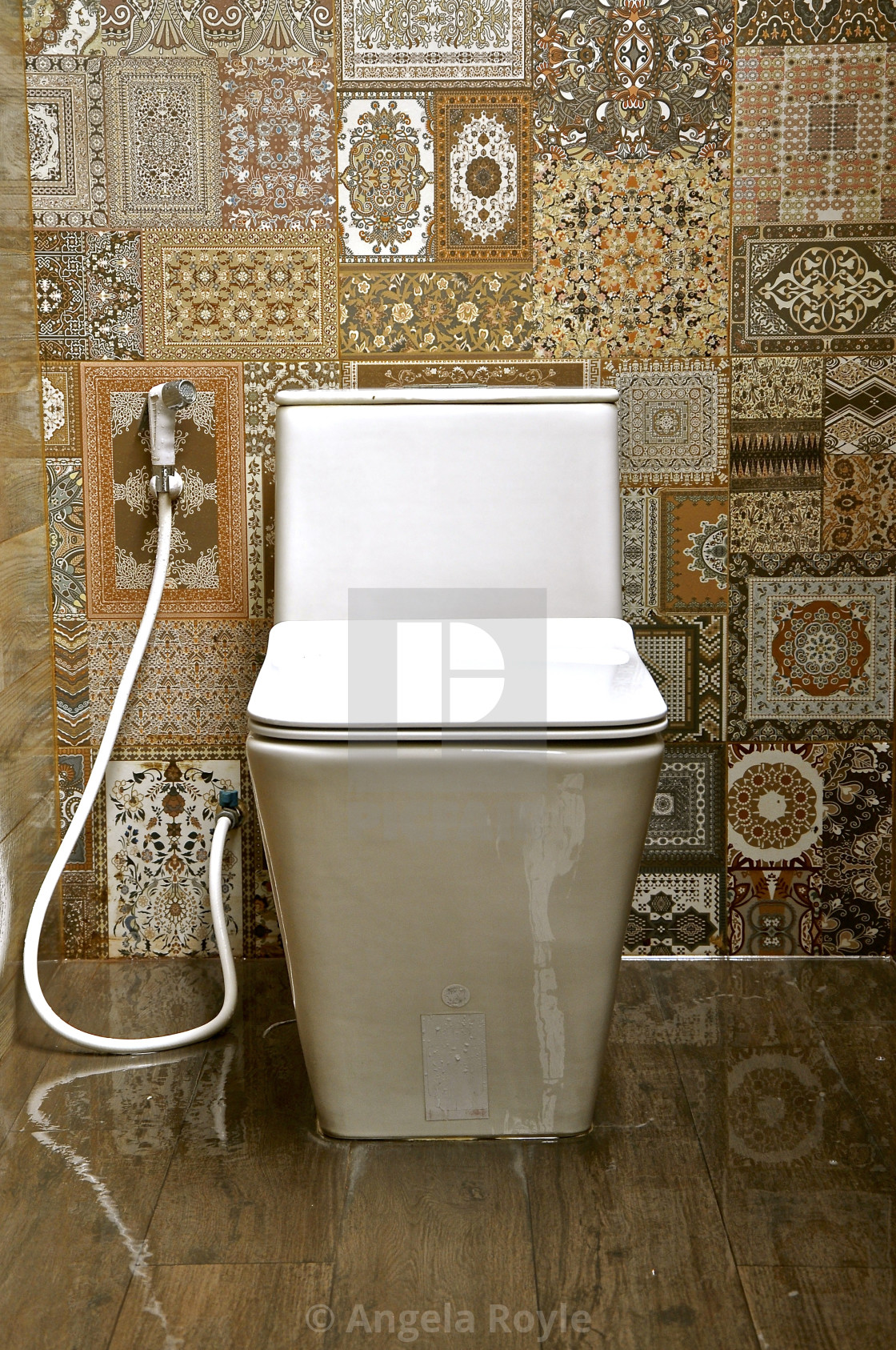 White ceramic toilet in a tiled room - License, download or
