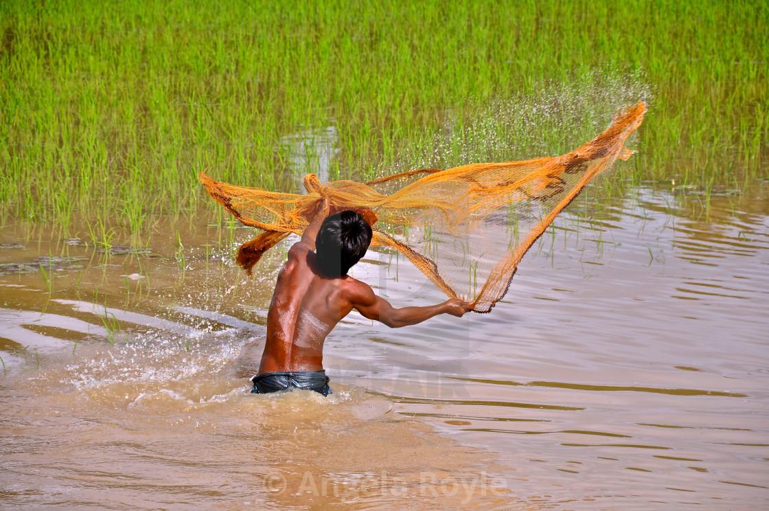 """Fisherman throwing a fishing net"" stock image"