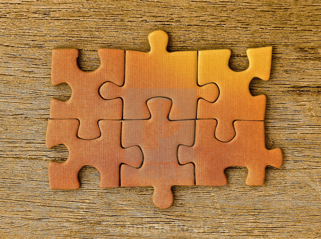 """Yellow jigsaw pieces on a wooden background"" stock image"