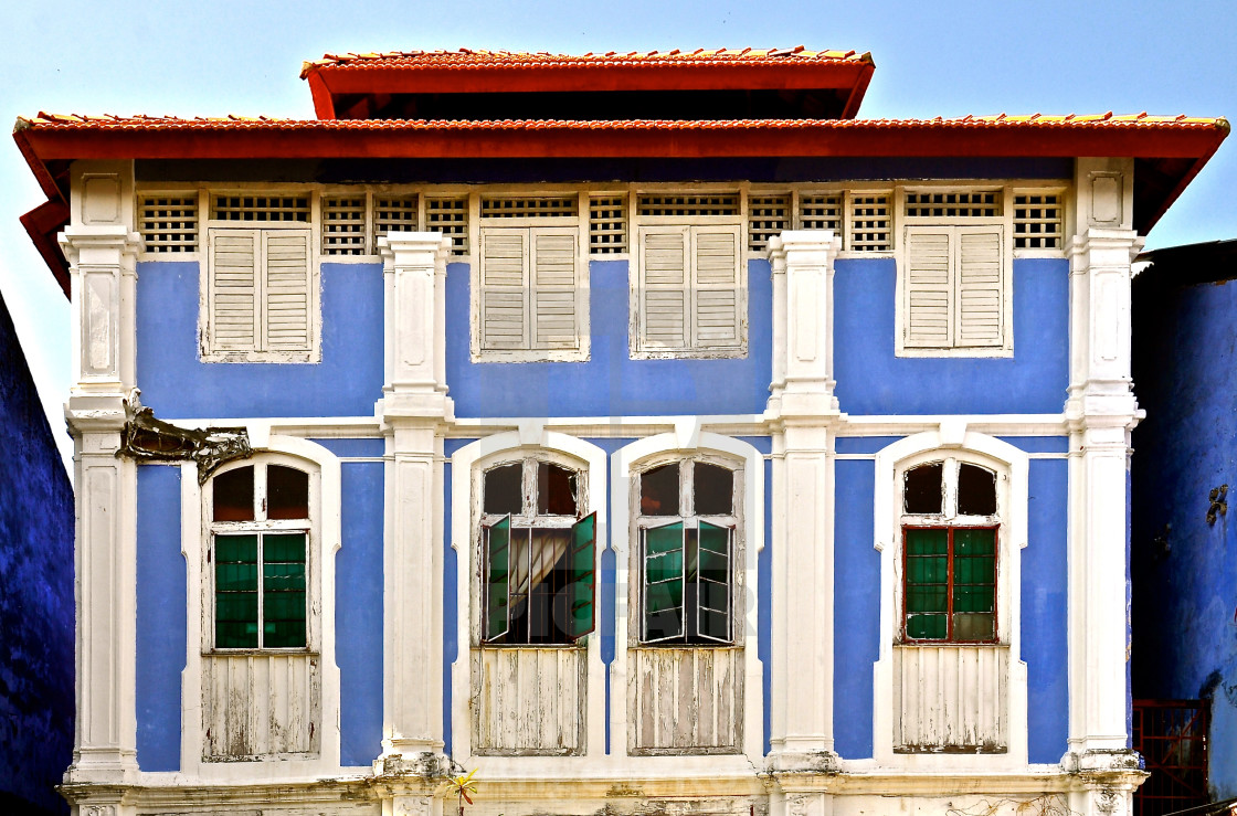 """Light blue pernakan shophouse with green windows and white shutters."" stock image"
