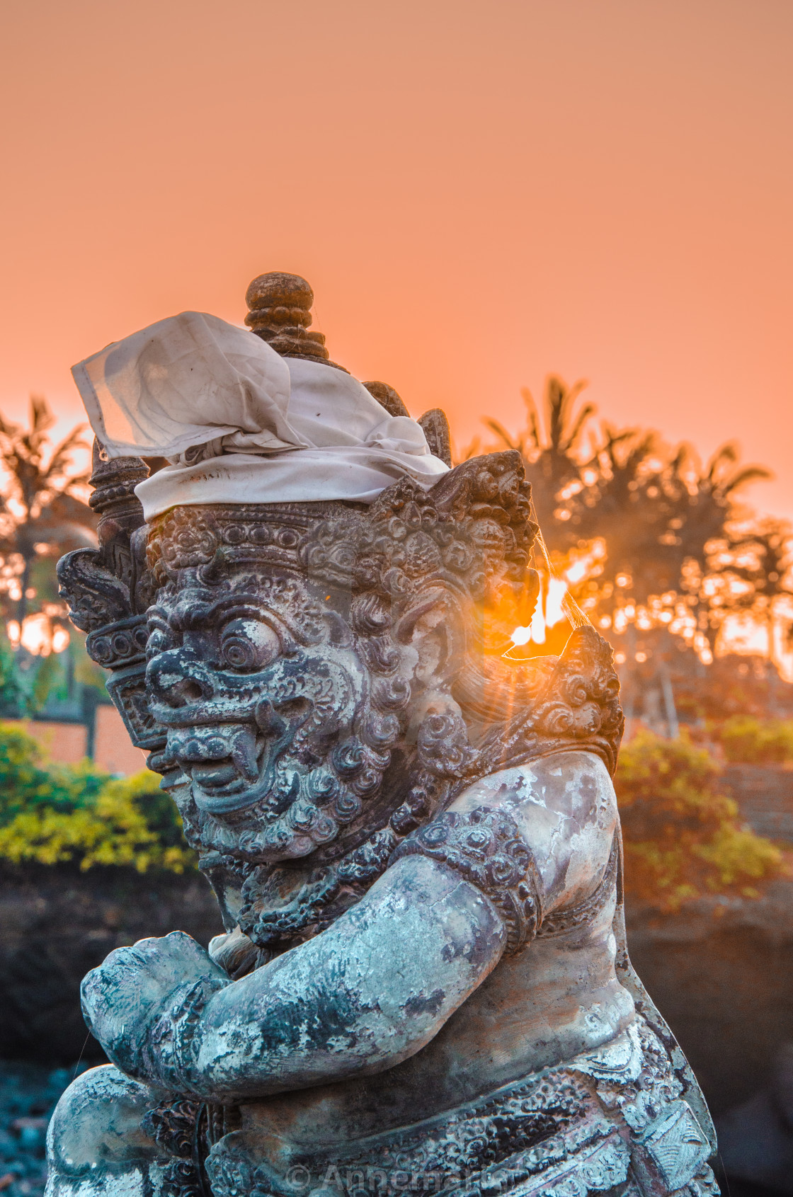 """Orange sky at sunrise with religious Balinese icon"" stock image"