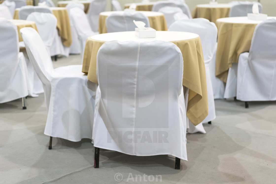 """Empty tables in a cafe covered with white table"" stock image"