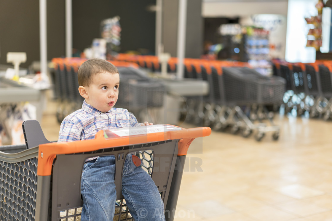 """Toddler in the cart in the supermarket"" stock image"