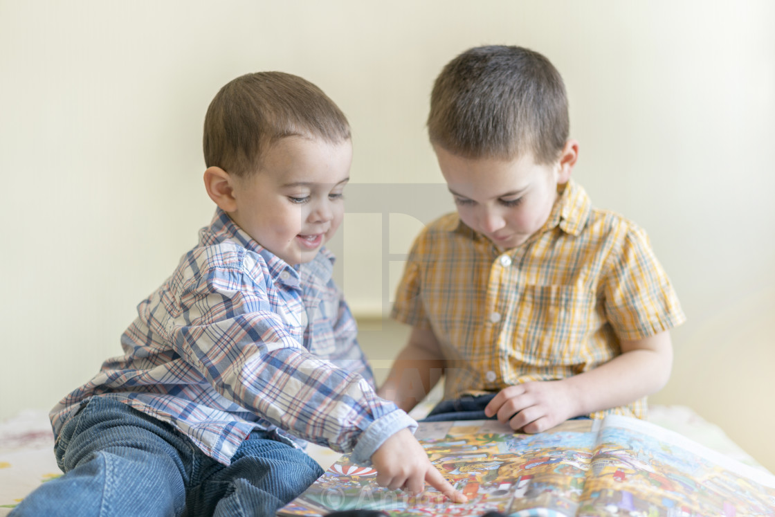 """Two cute little boys are studying a book. Two little boys in shirts with a..."" stock image"