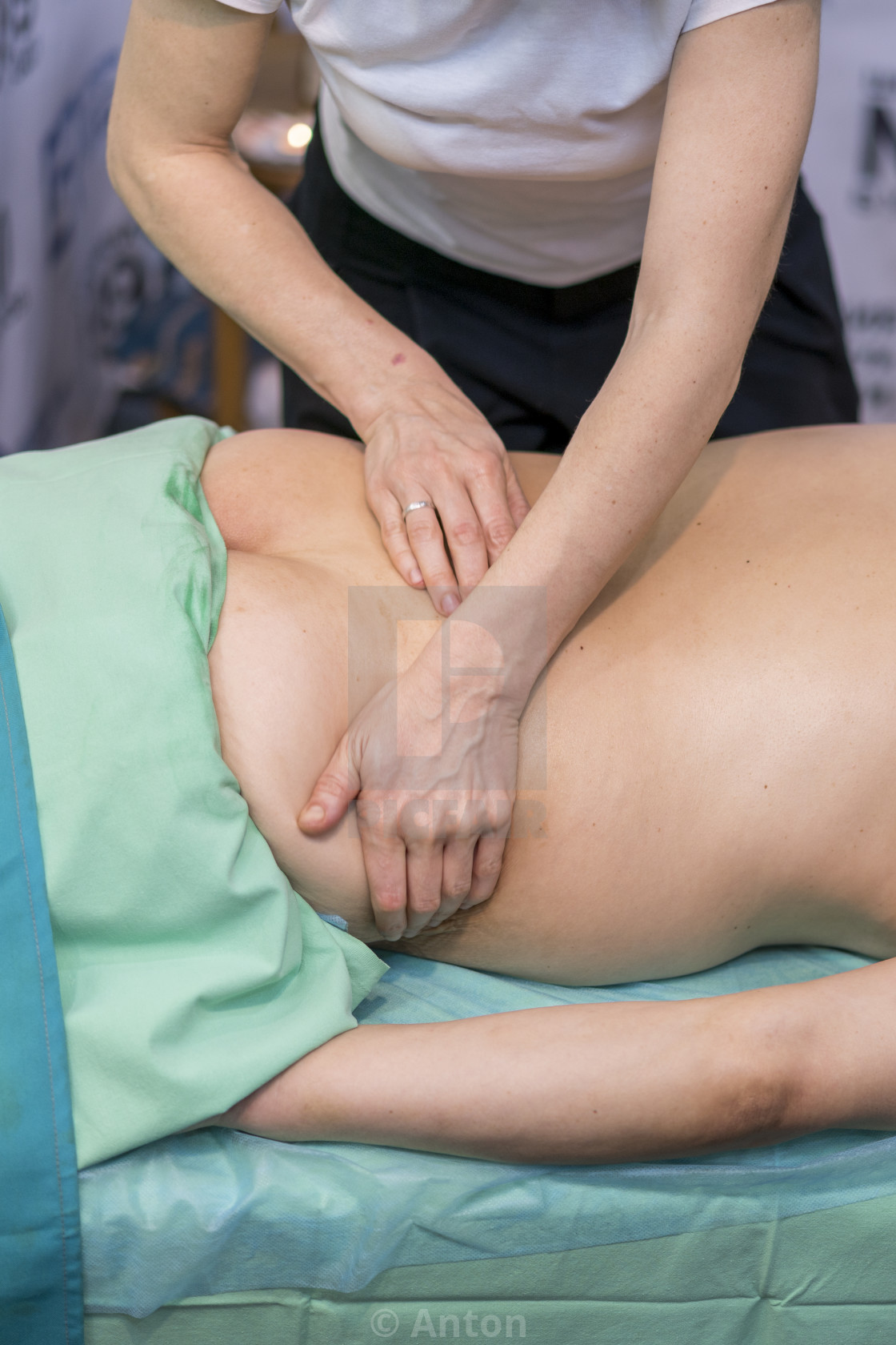 """Physiotherapist doing shoulder massage to patient in a medical office"" stock image"