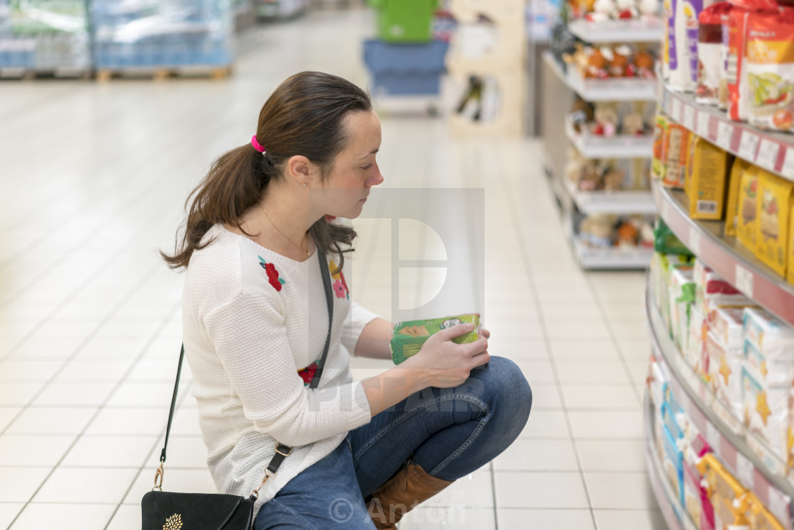 """middle-aged woman picks food in a supermarket"" stock image"
