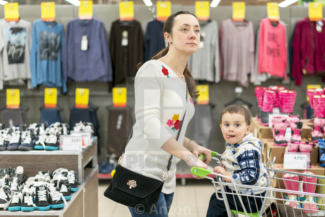 """""""Mom with a child in a trolley in a shopping center. Mom with a small son in a..."""" stock image"""