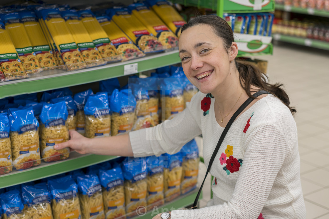 """Beautiful middle-aged woman choosing spaghetti in a store. Woman with a..."" stock image"