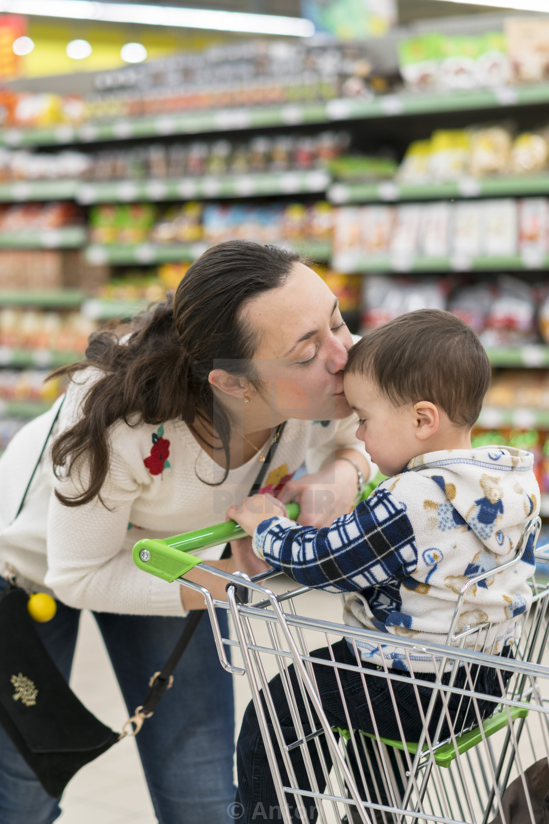 """Happy mother embracing and kissing her son in the store"" stock image"