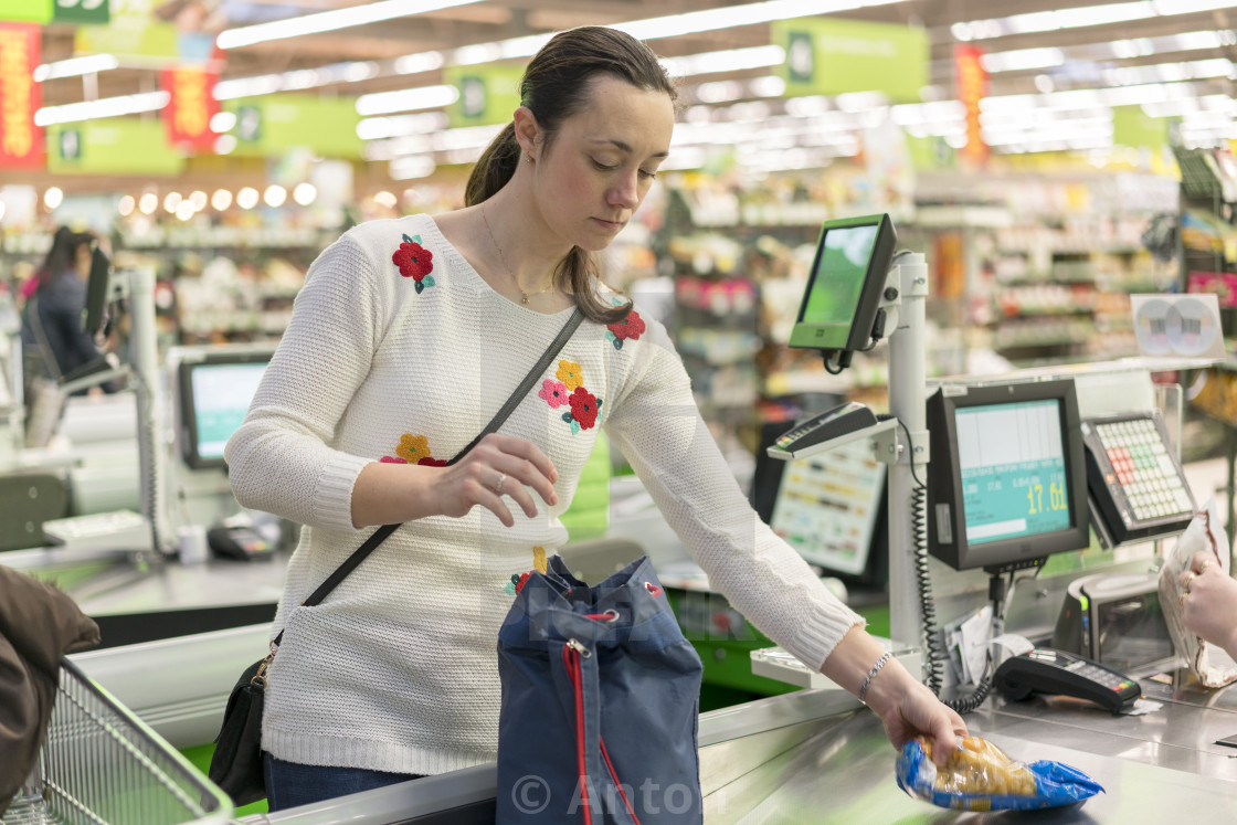 """Beautiful middle-aged woman at the checkout in the supermarket"" stock image"