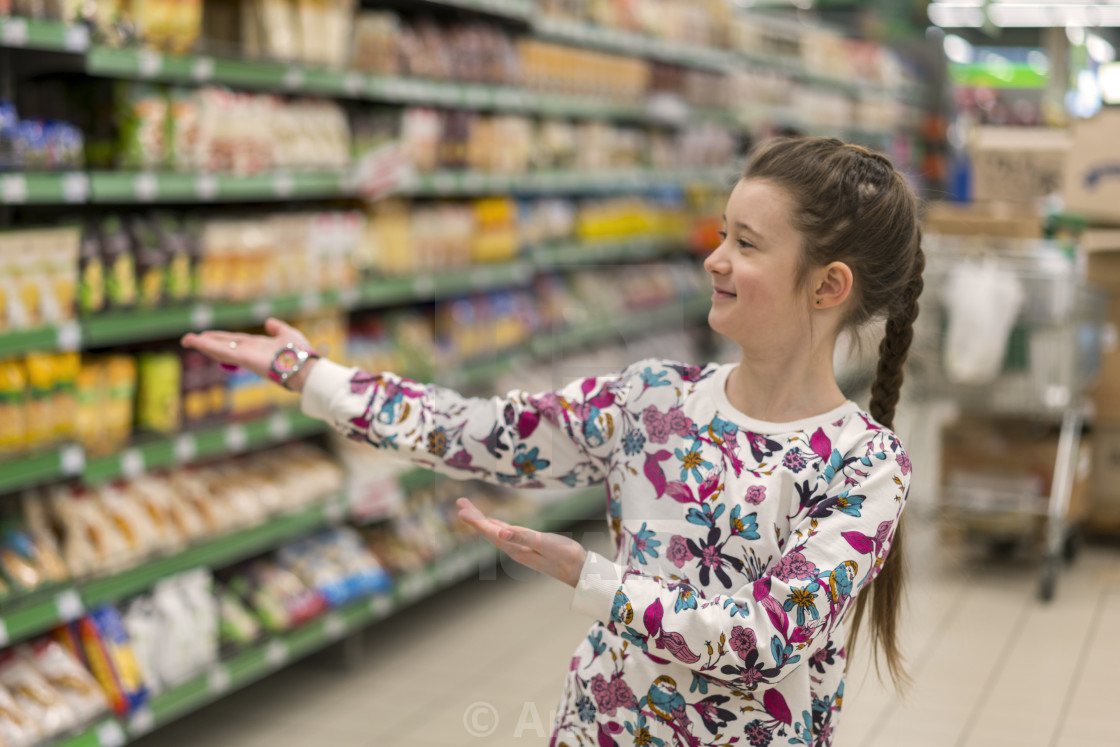 """Cheerful girl in a supermarket shows on products. A girl of 8 years in a..."" stock image"