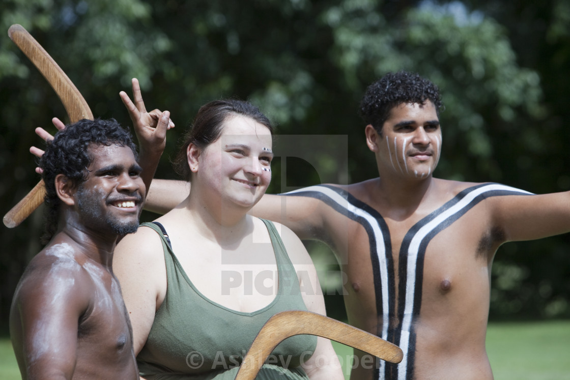 Tourists pose for photos with aboriginal people with