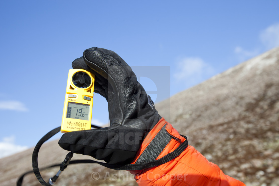 A mountaineer using an anenometer to measure wind speed and