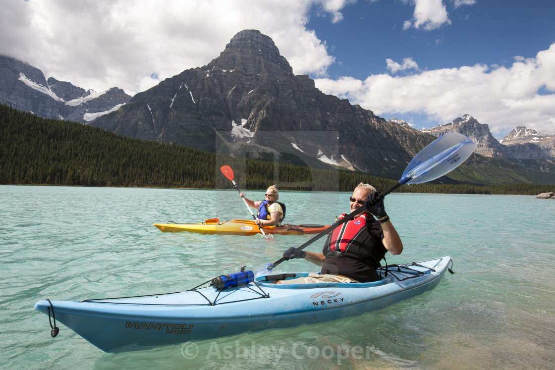 """A Canadian couple kayaking on Waterfowl Lake in the Canadian Rockies."" stock image"