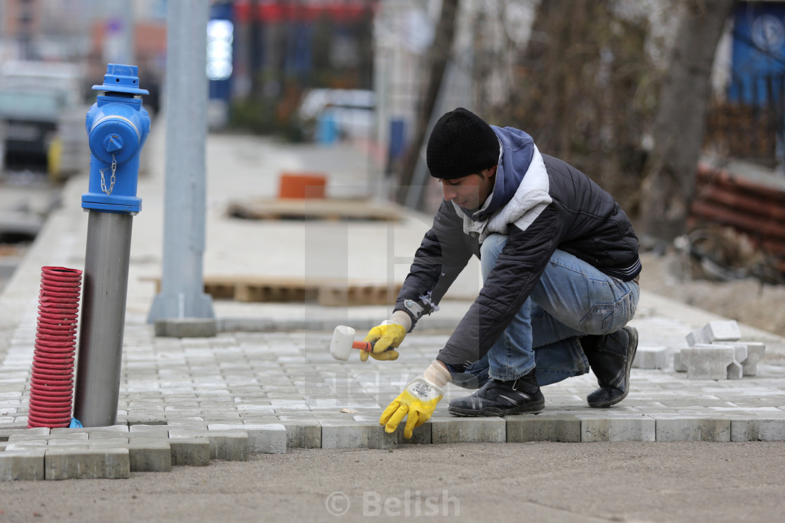 """Paving stone worker"" stock image"