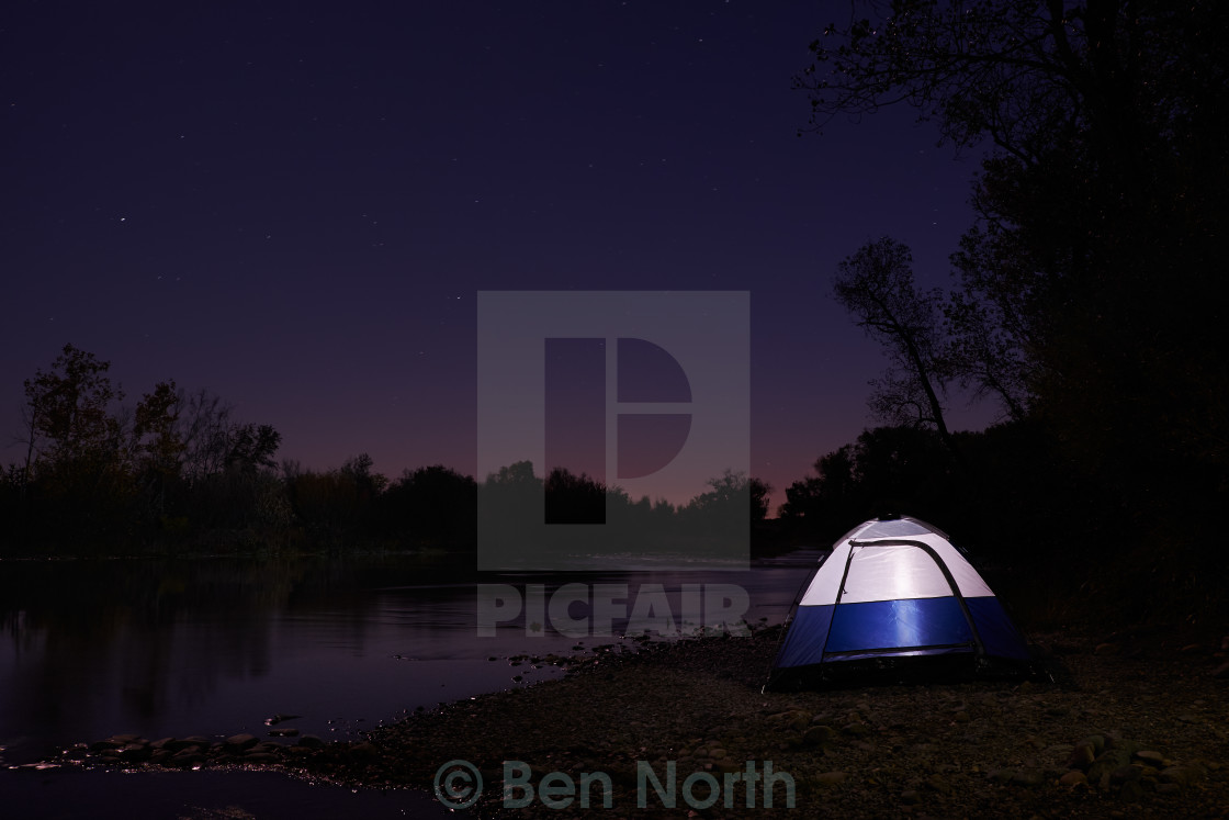 """Tent on the Edge of A River at Night"" stock image"