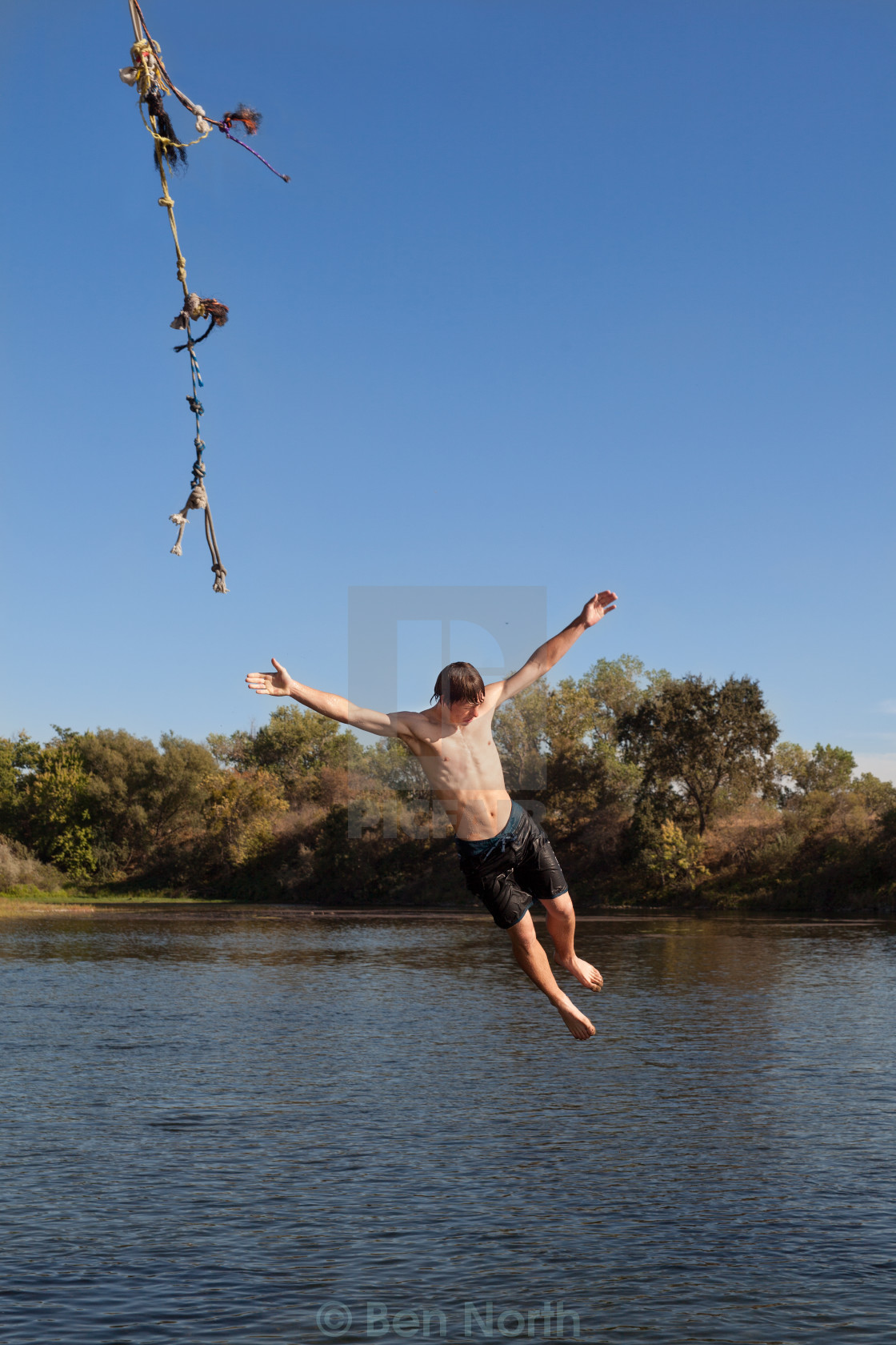 """Tenage Boy Letting Go Of A Rope Swing"" stock image"
