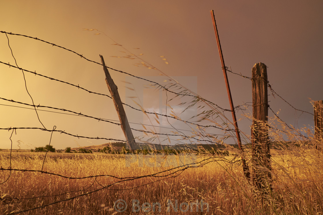 """Old Broken Fence In a Field After a Storm"" stock image"