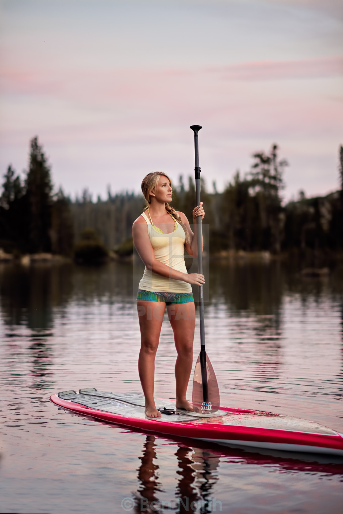"""A Young Woman Resting on a Paddle Board at Sunset"" stock image"