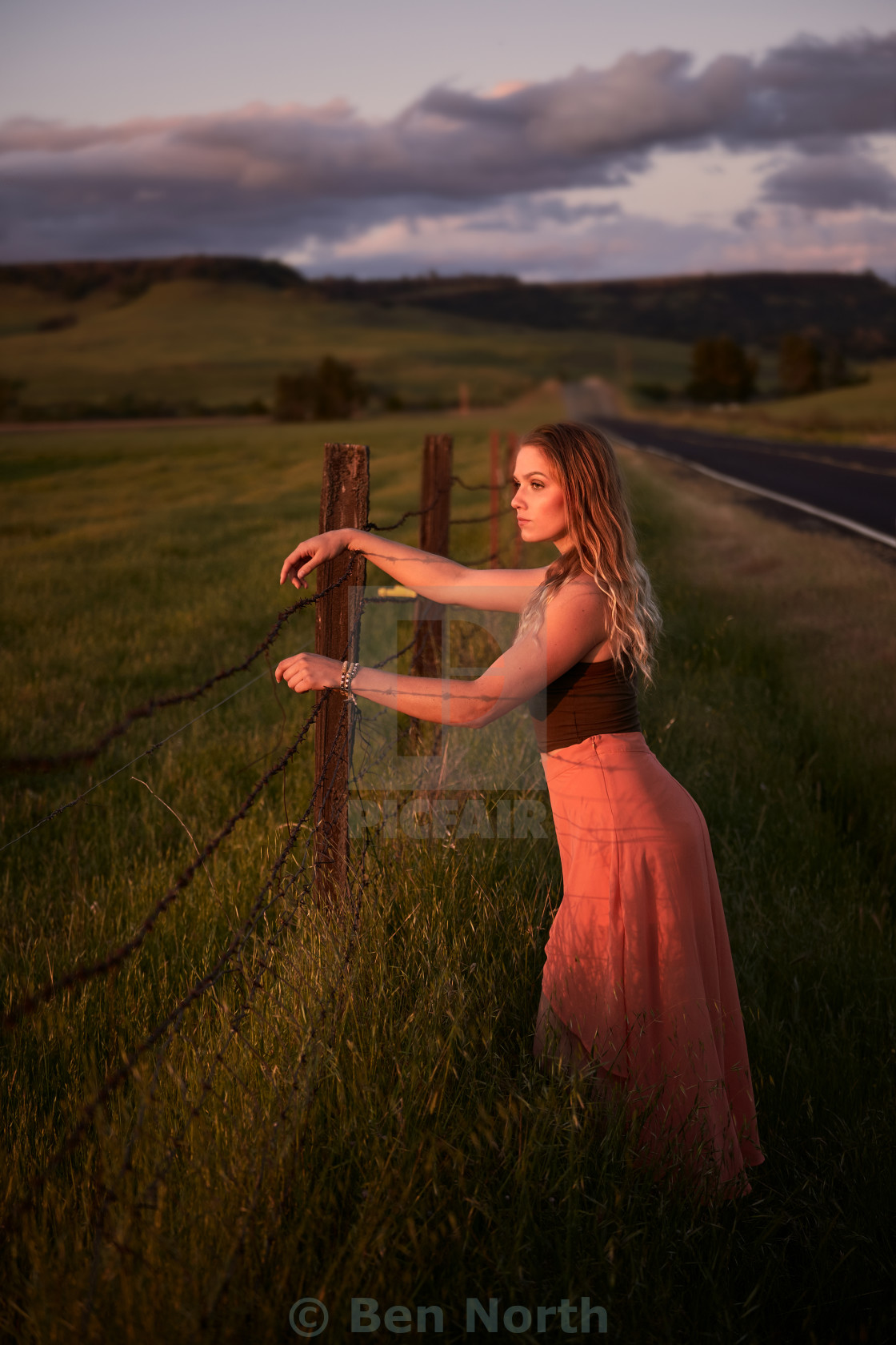"""""""Young Woman in a Long Skirt Leaning on a Cattle Ranch Fence."""" stock image"""